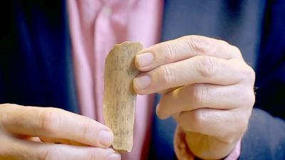 man holding a piece of bone with Chinese characters etched into it
