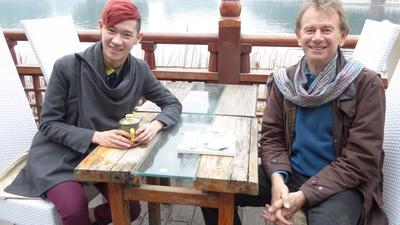 Michael Wood sitting at a table by a lake with a young stylishly-dressed Chinese man