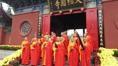 monks standing on steps in front of a temple holding musical instruments