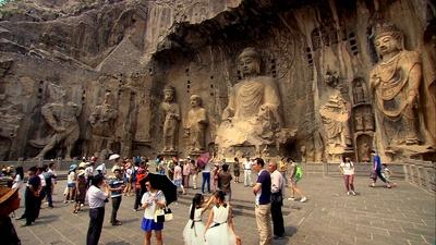 Tourists in front of large Buddhist statues carved into a clif