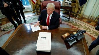 News Wrap: Trump signs GOP tax bill into law