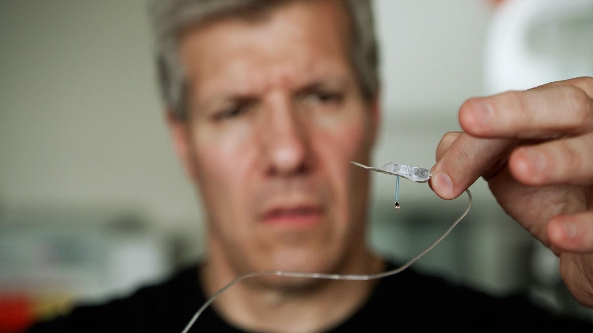 A close-up of Ed Damiano holding up a medical device. Part of his work towards creating a bionic pancreas.