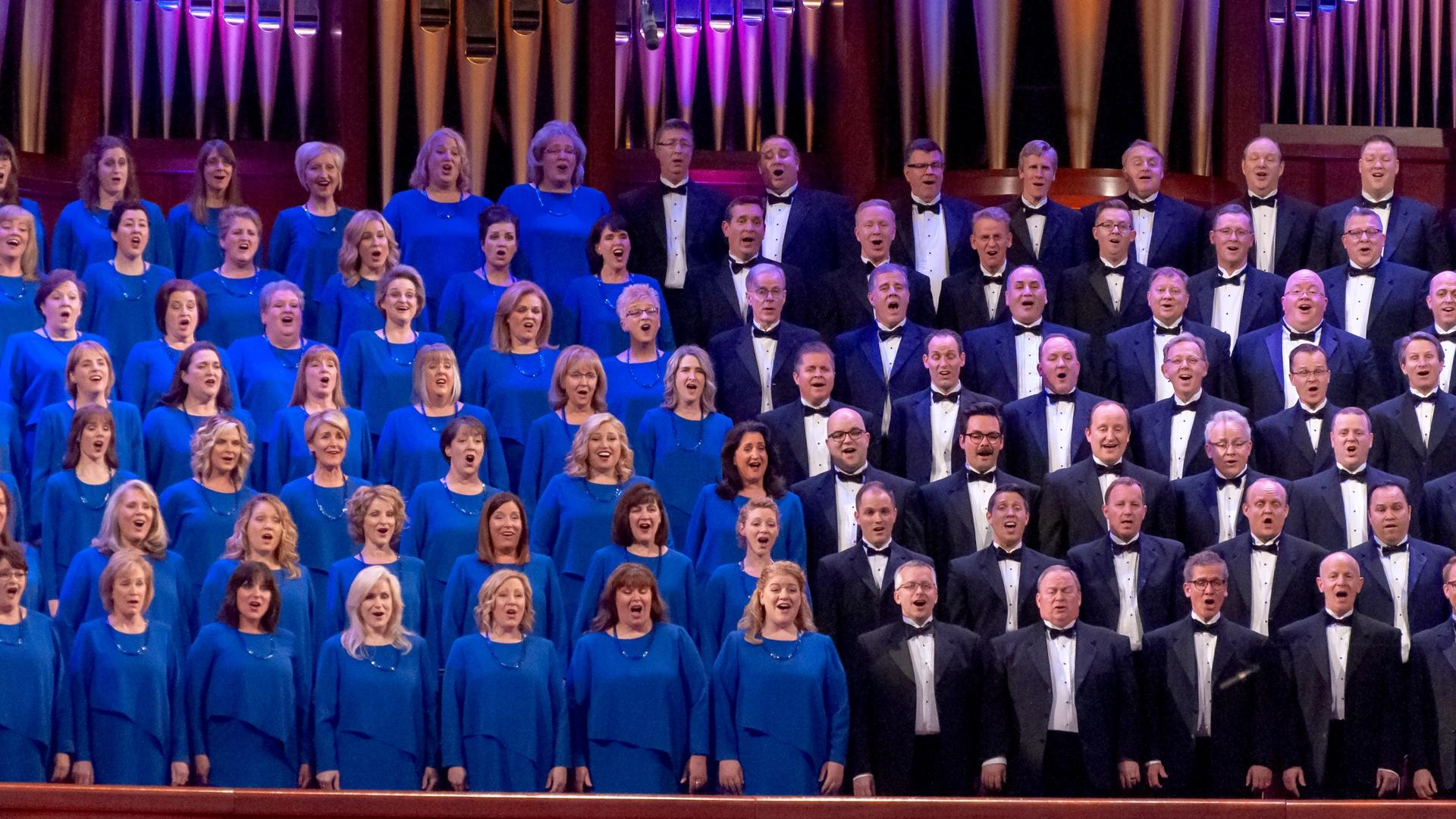Female members of The Tabernacle Choir singing with Christmas decorations and a pipe organ behind them.