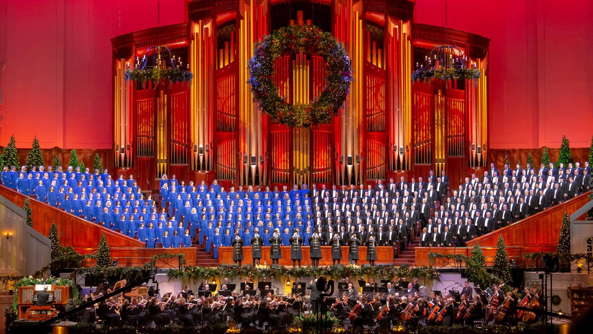 The Tabernacle Choir performs alongside conductor Mack Wilberg and the Orchestra at Temple Square in front of a large organ and festive Christmas decorations.