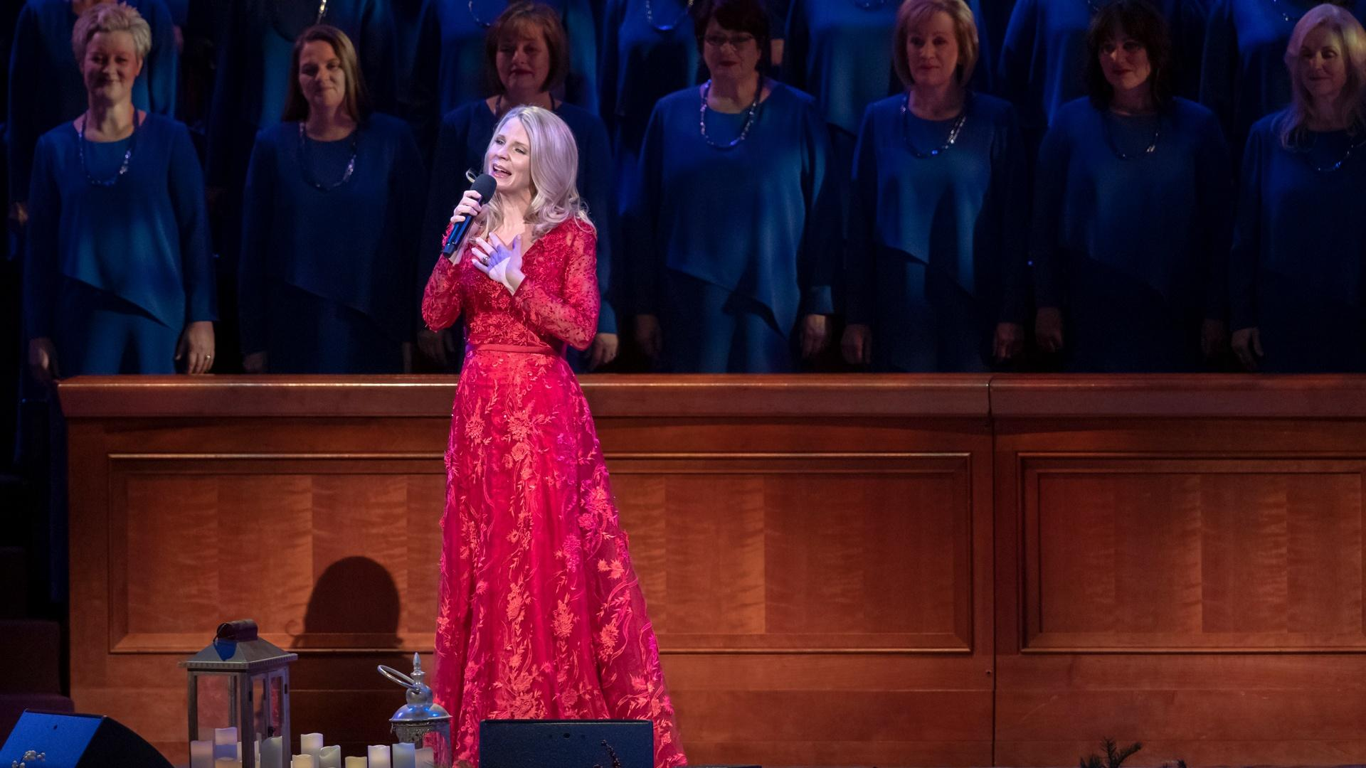 Kristin Chenoweth sings in front of the organist and musicians holding jingle bells.