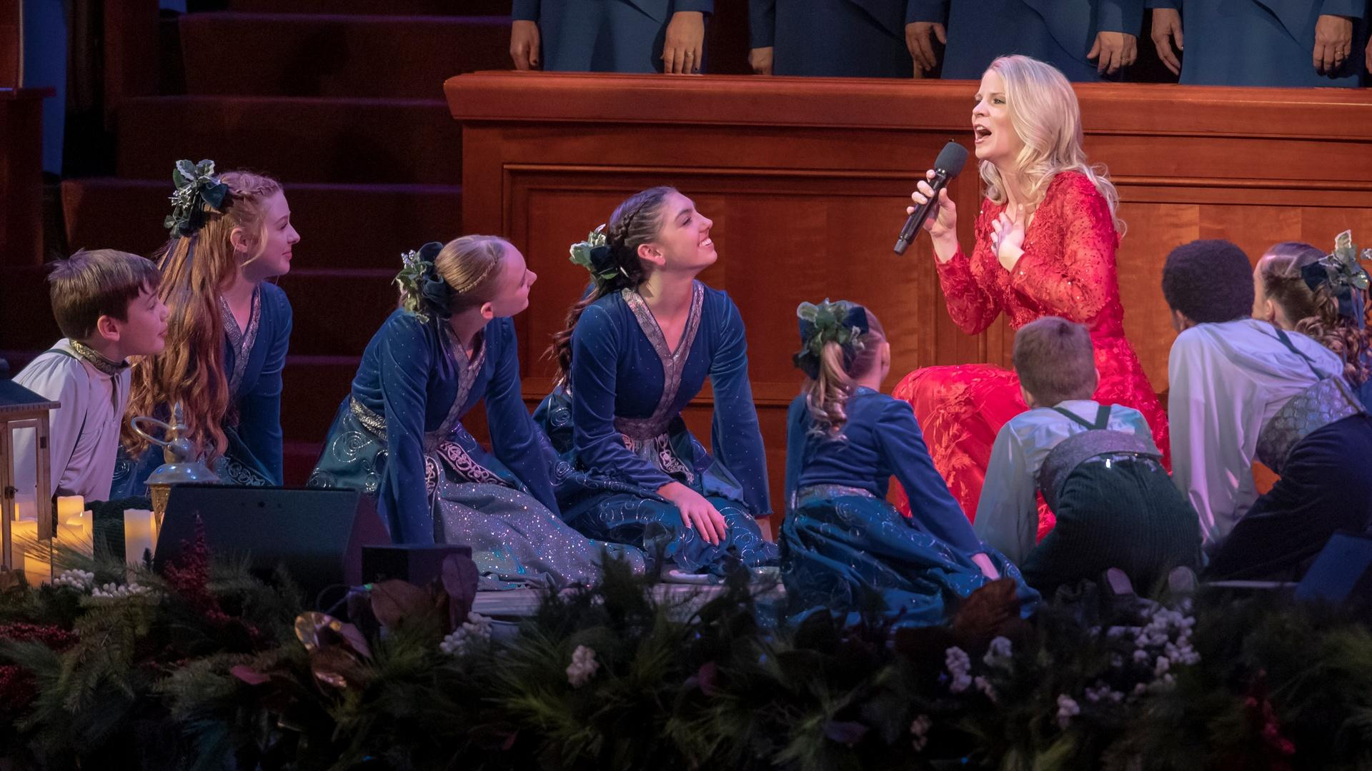 Kristin Chenoweth sings into a microphone amidst the female members of The Tabernacle Choir, who are all dressed in white with single-color scarves.