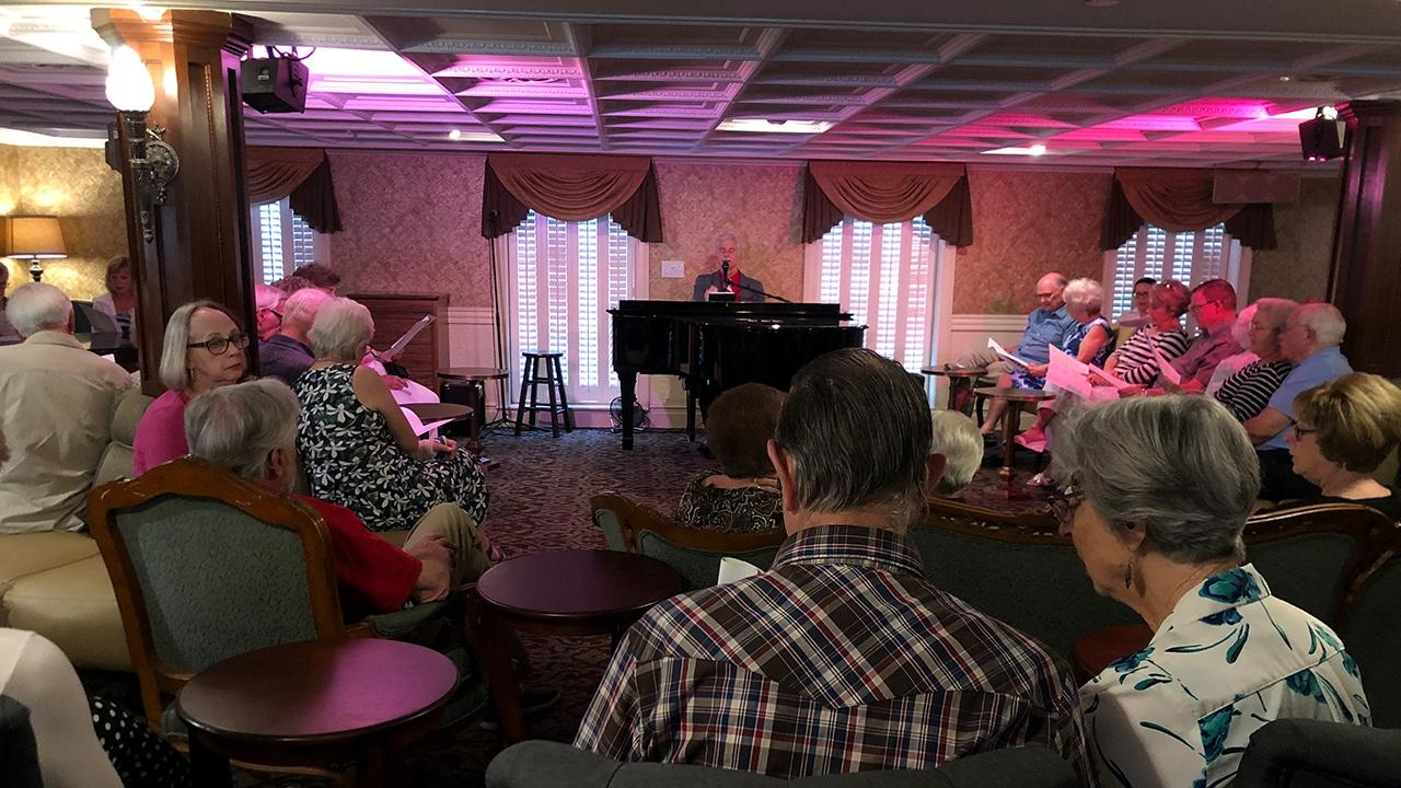 guest enjoying piano music in the main lounge of the American Queen
