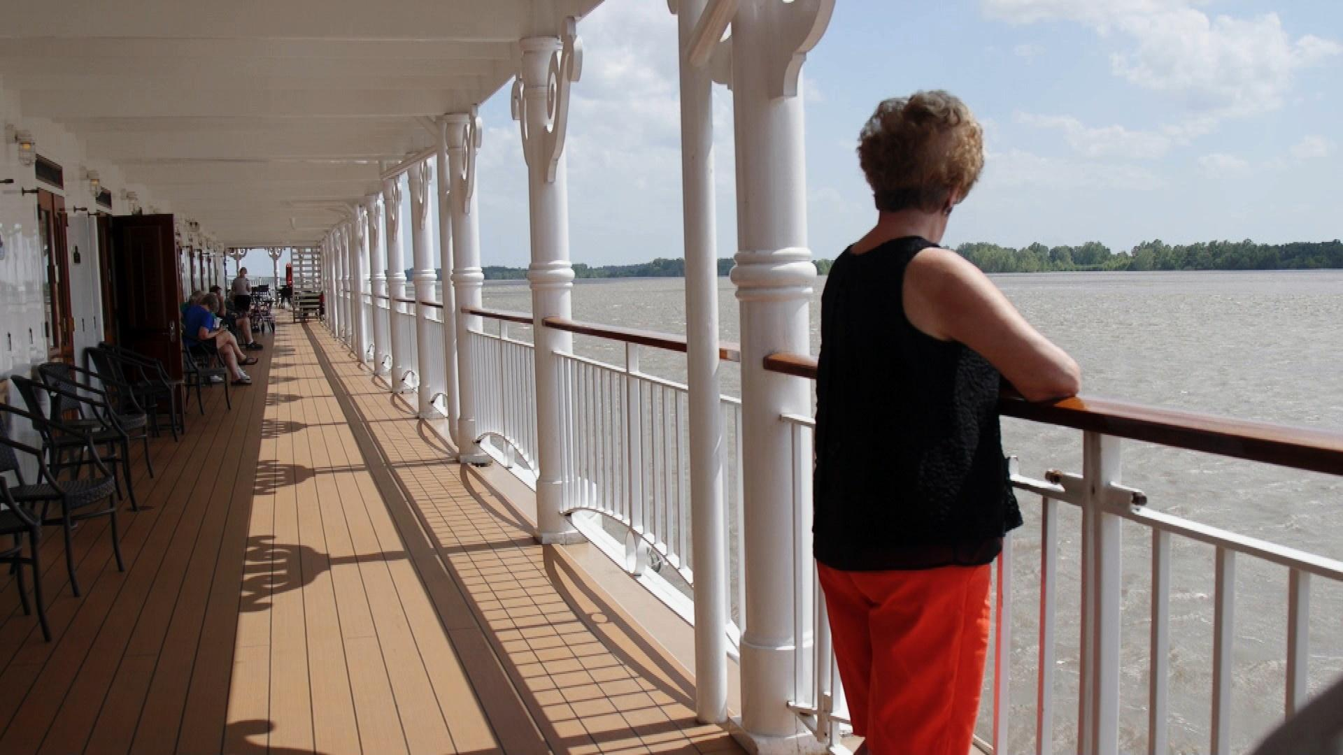 woman on deck of boar looking out to the waters of the Mississippi River.