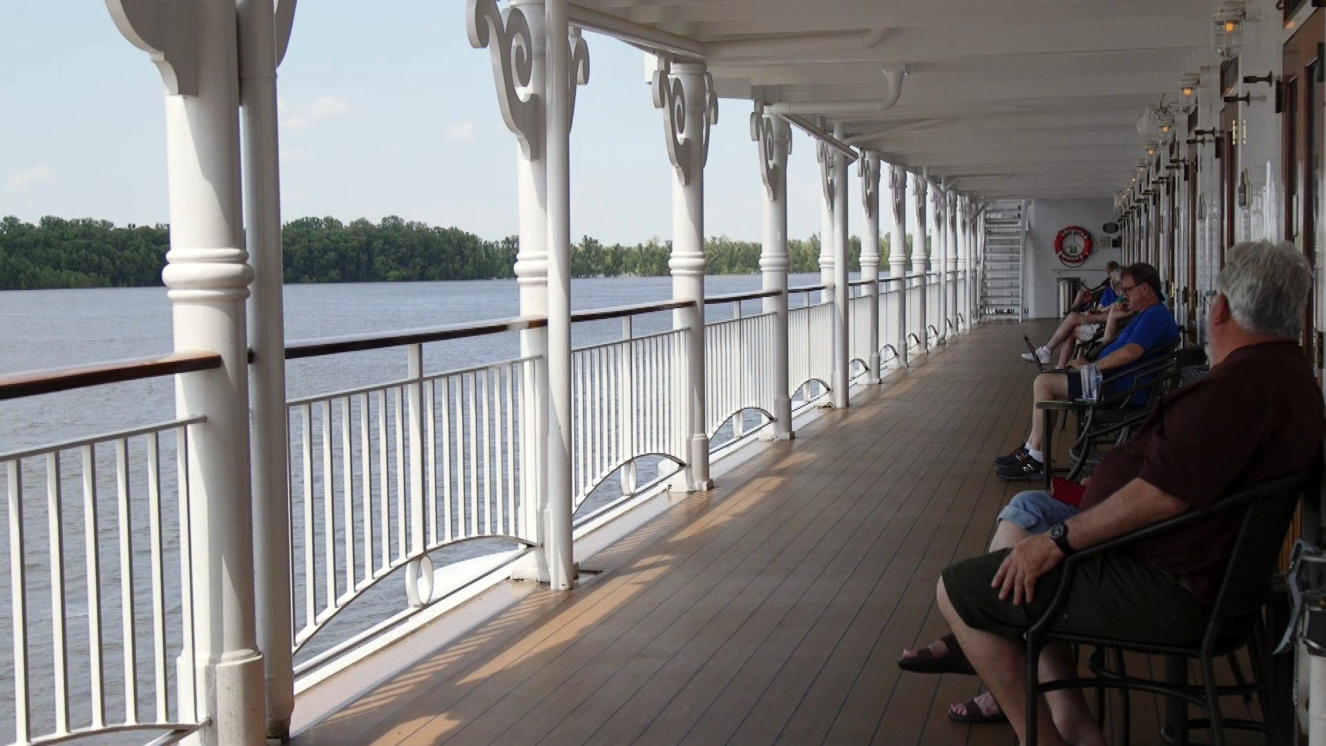 passengers sit along the veranda aboard the American Queen