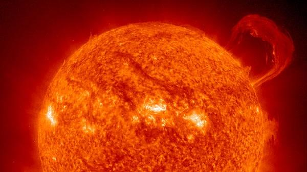 close-up of the sun with a solar flare at the top right