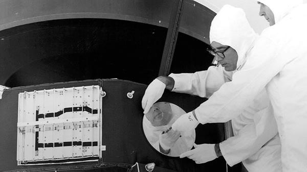 engineers attaching disc to Voyager spacecraft