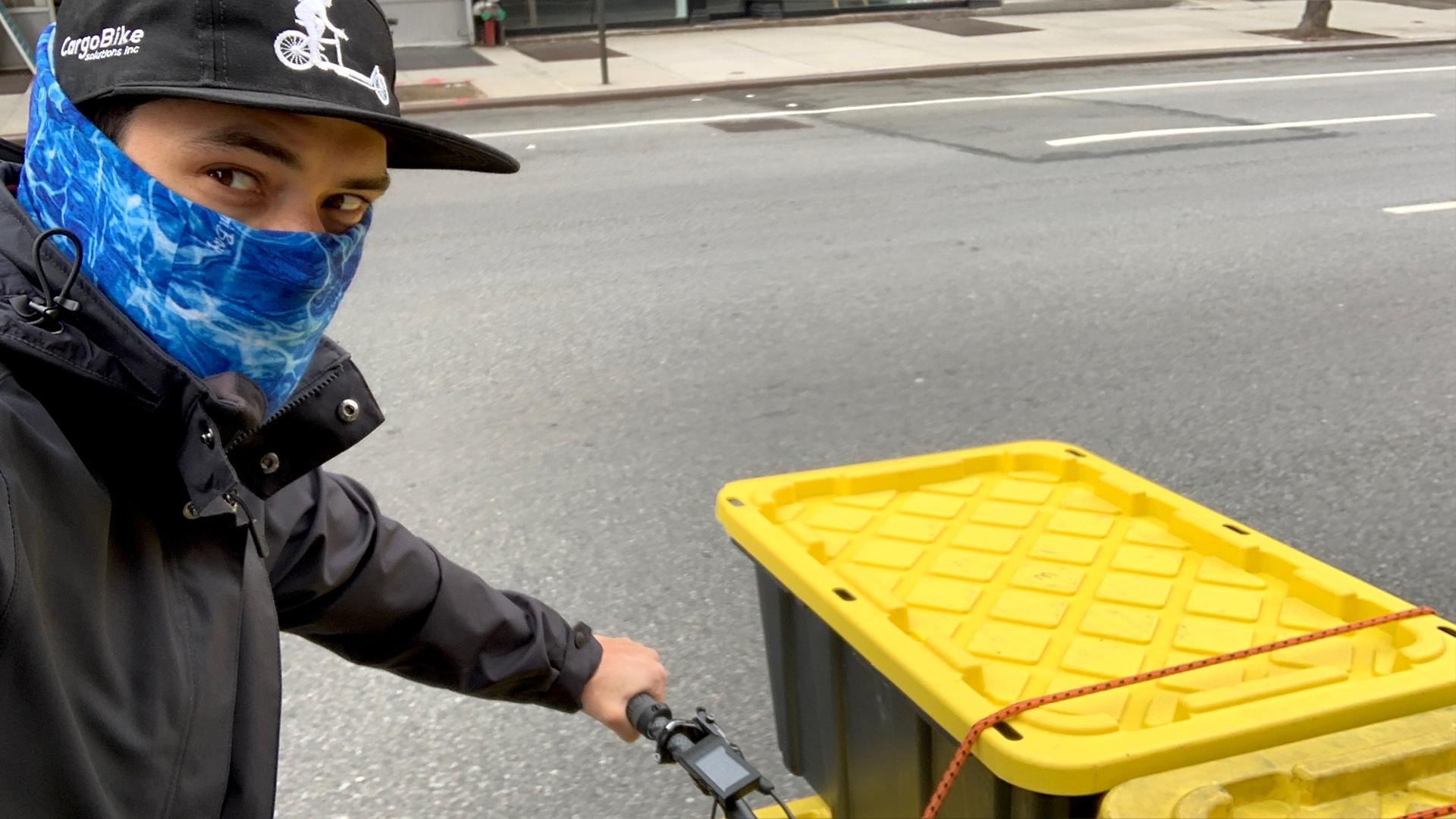 Diego - in a mask rides his courier bike