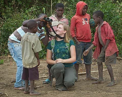 Heidi Ware lets young children look through her binoculars in Gorongosa