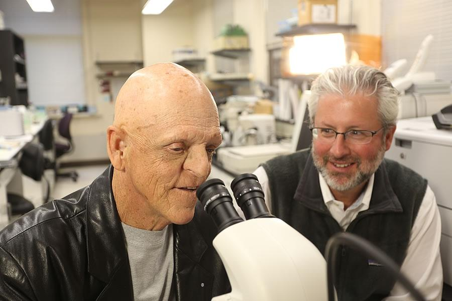 Michael Berryman looks through a microscope with Neil Shubin sitting next to him