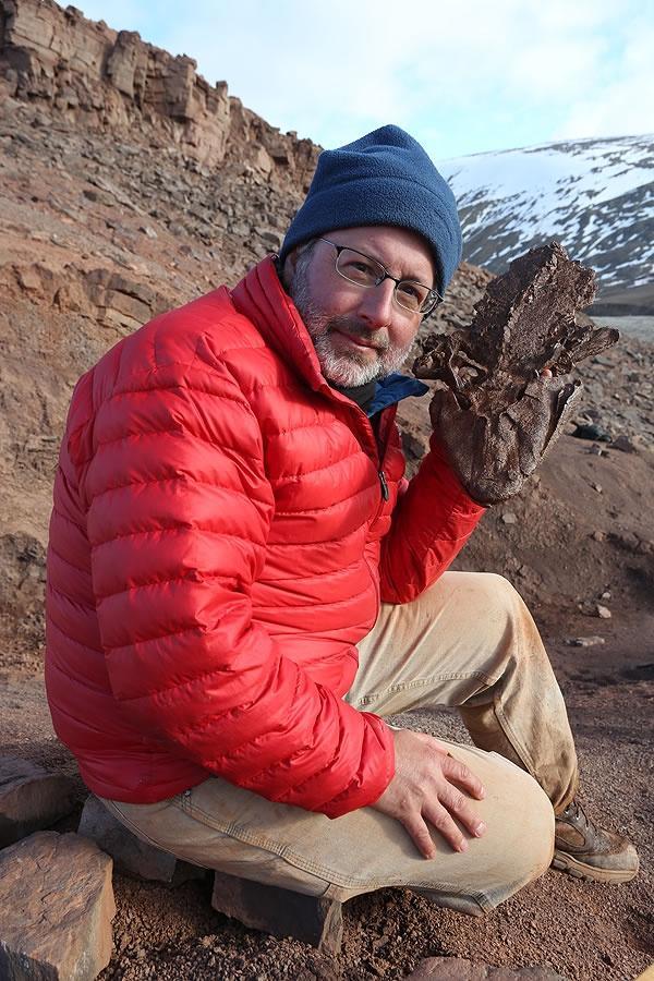 Neil Shubin holding up a cast of a fossil