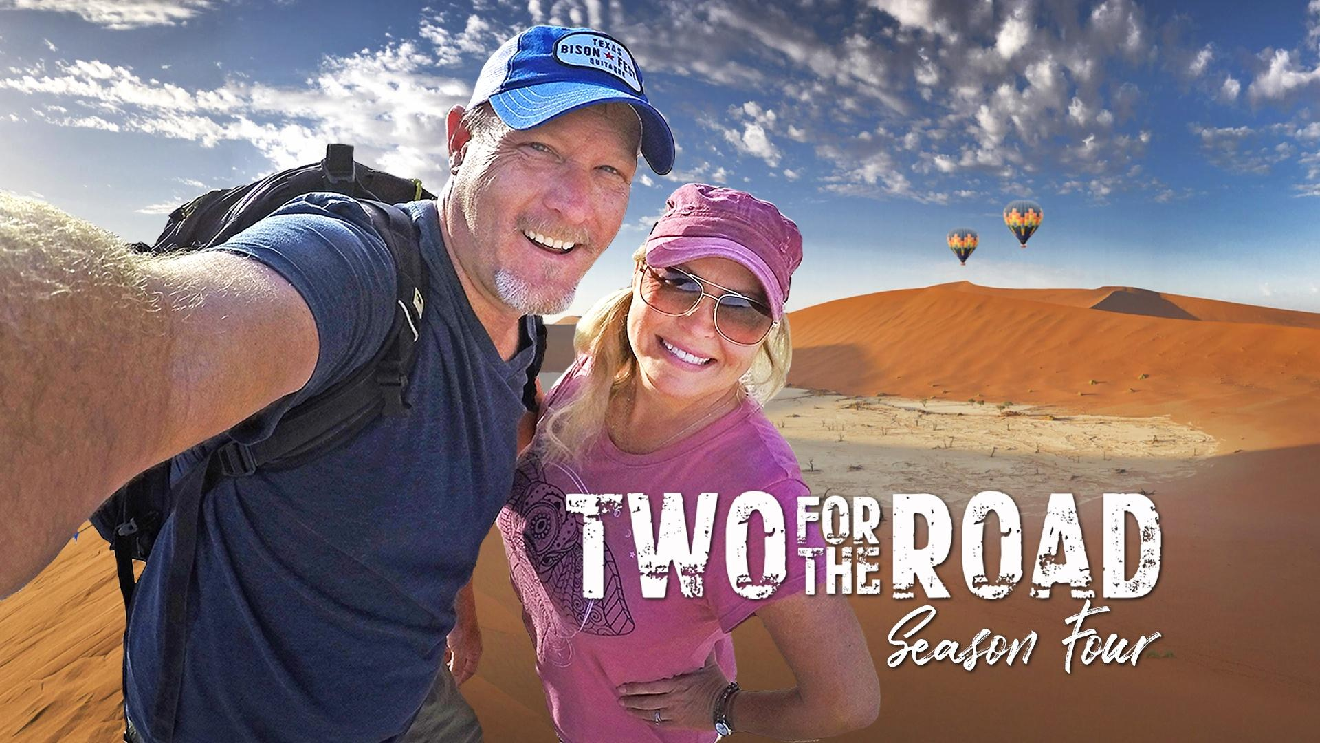 Nik and Dusty Green stand in front of sand dunes with the Two for the Road logo in front of them.