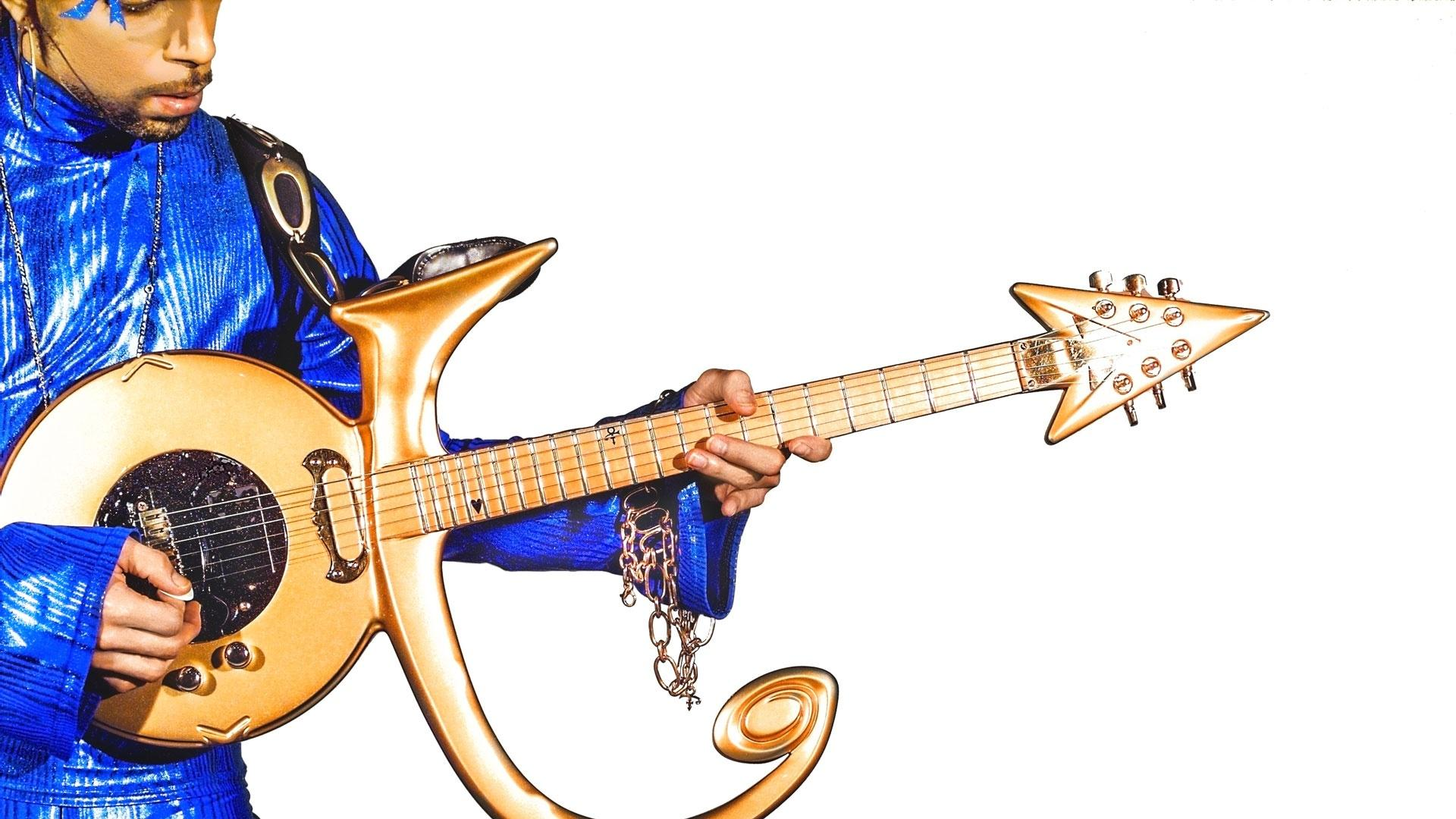 Prince in blue with gold symbol guitar
