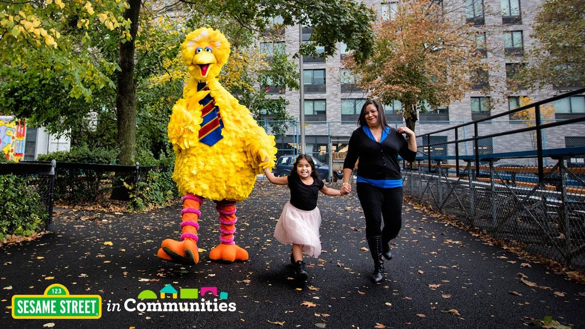 Big Bird and mom and girl holding hands down street. Sesame Street in Communities logo