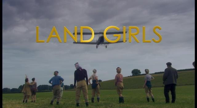 group of women in a field staring up at a plane