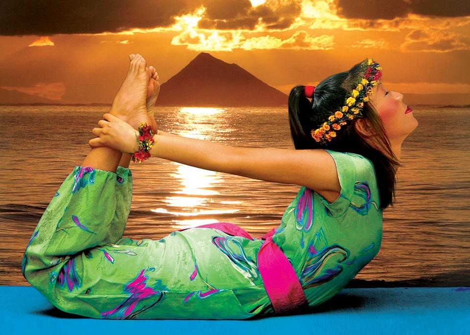 woman in yoga pose in front of sunset background