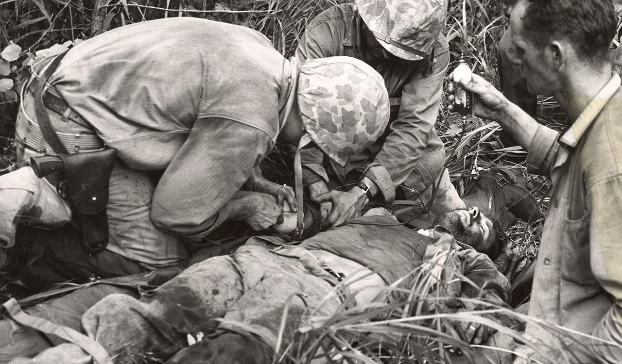 Members of the Seventh Marine Regiment assit a Navy Corpsman as he gives blood to a Marine hit by an enemy hand grenade