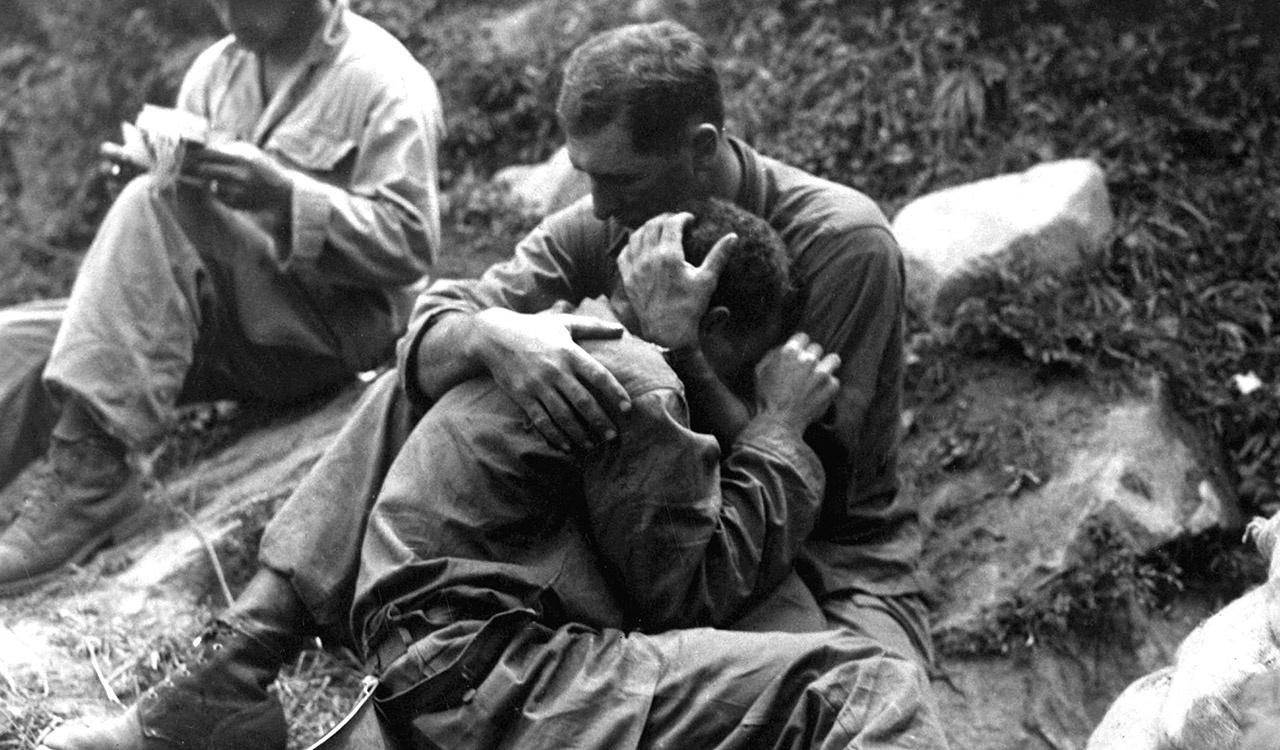 A grief stricken American infantryman whose buddy has been killed in action is comforted by another soldier. In the background a corpsman methodically fills out casualty tags, Haktong-ni area, Korea.
