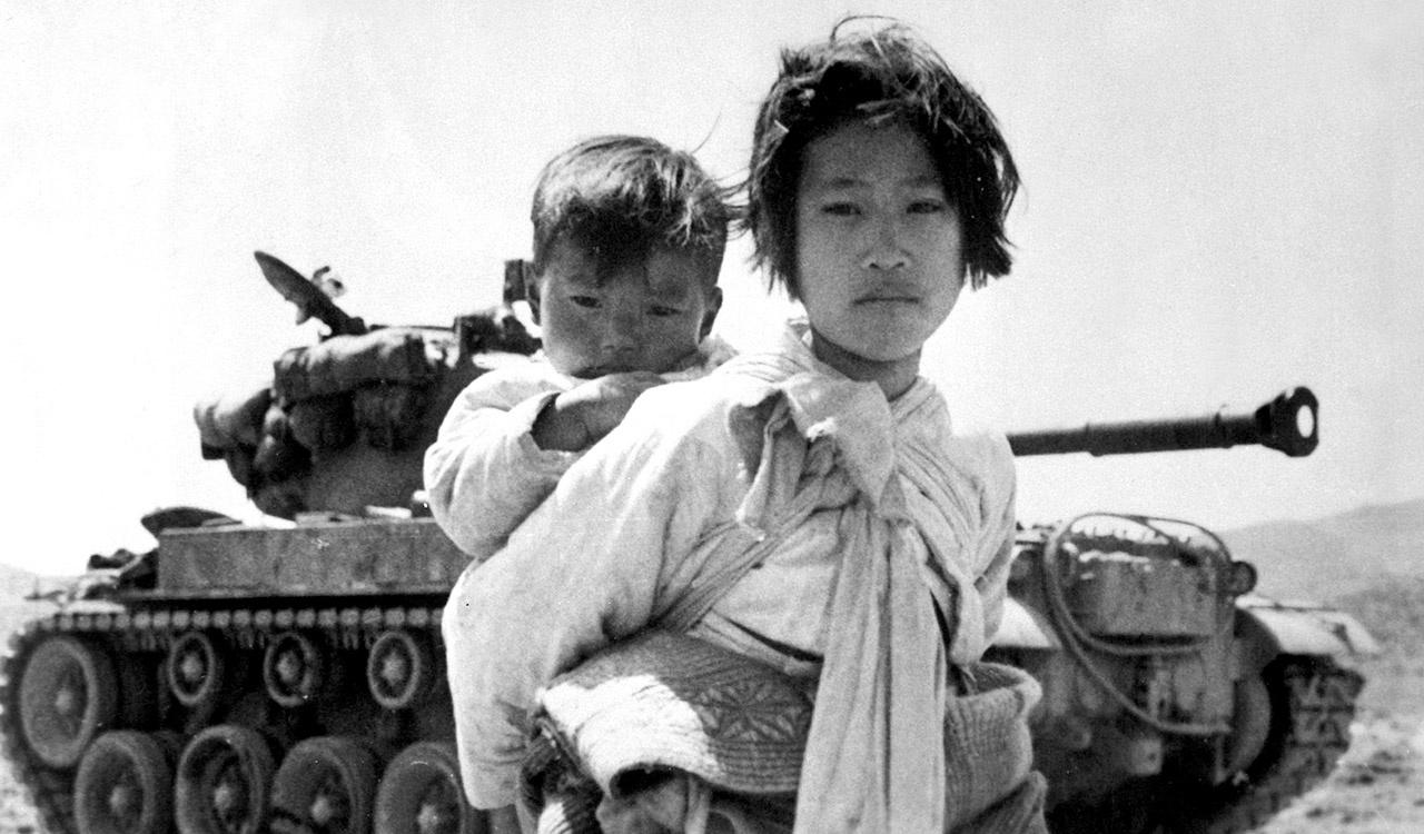 With her brother on her back a war weary Korean girl tiredly trudges by a stalled M-26 tank, at Haengju, Korea, 6/9/51