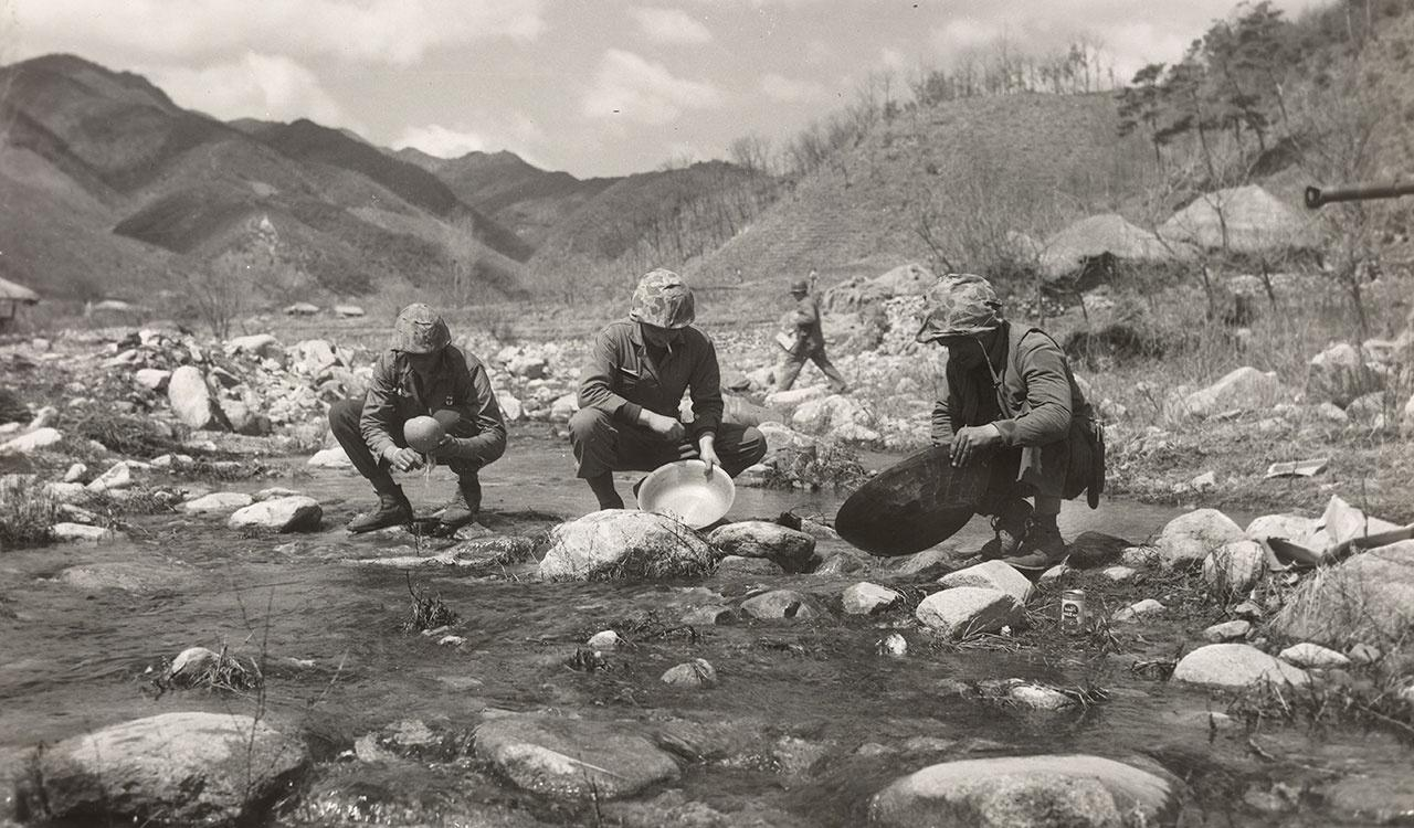 """Leatherneck """"Forty-Niners"""" take a unique break from the war to pan a small stream a few mile north of Chaunni after hearing rumors of gold"""