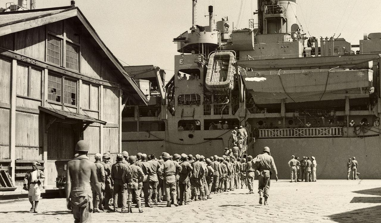 Marines pulled out of the lines in South Korea, board ship for a welcome hot meal. Replacements from States, right, look on. Sept. 5, 1950.