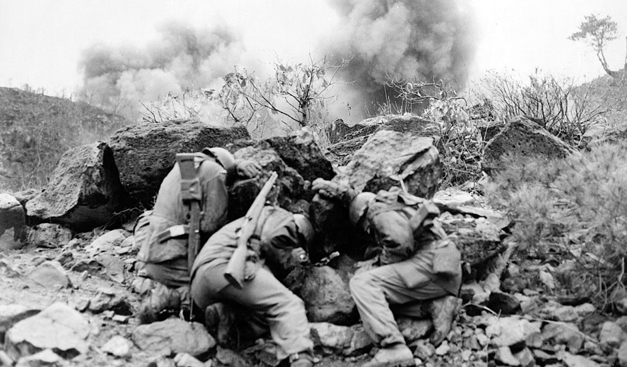 Men covering up behind rocks to shield themselves from exploding mortar shells