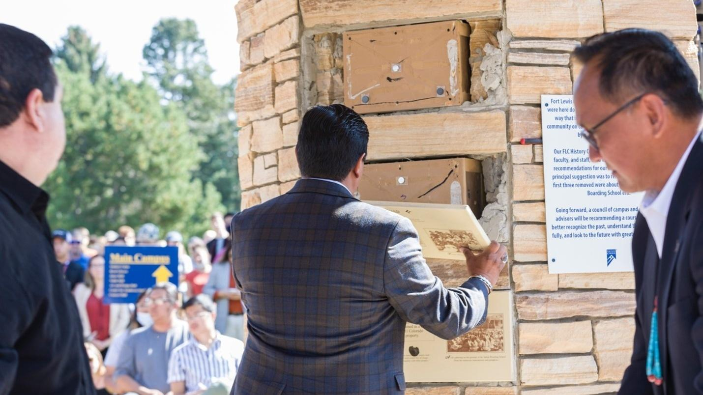 School officials remove the inaccurate panels from the clock tower at Fort Lewis College. The panels misrepresented the history of the former Indian Boarding School at Fort Lewis.