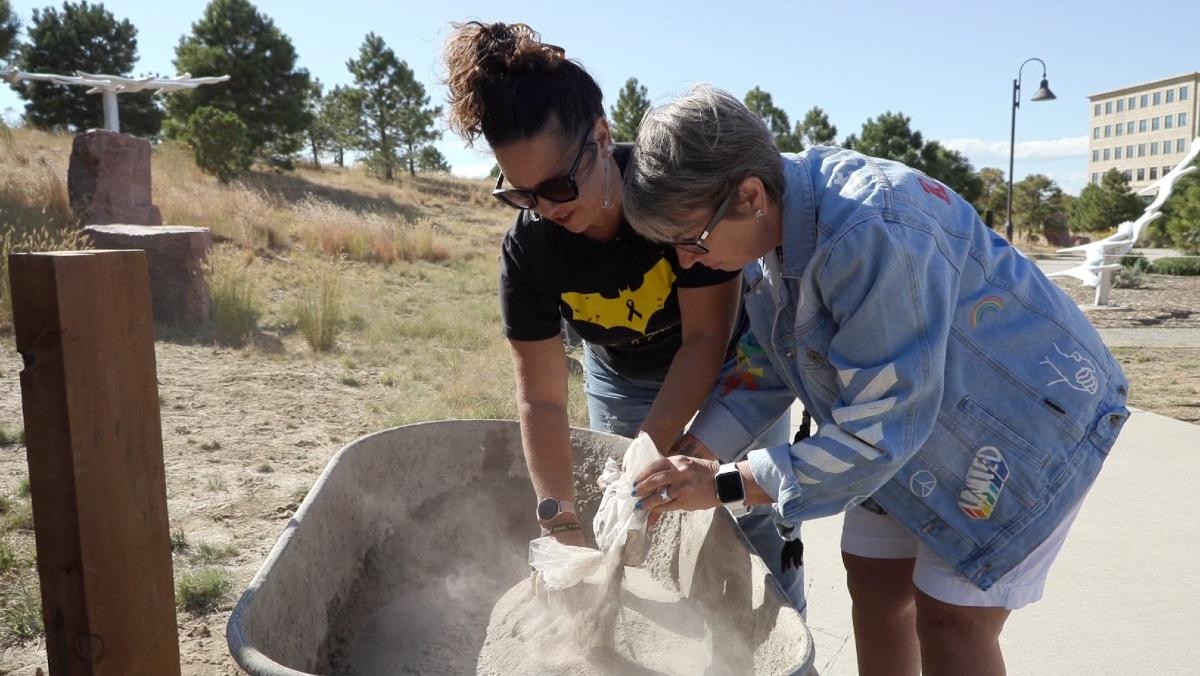 Heather Dearman of the 7/20 Memorial Foundation mixes ashes into the cement for the little lending library