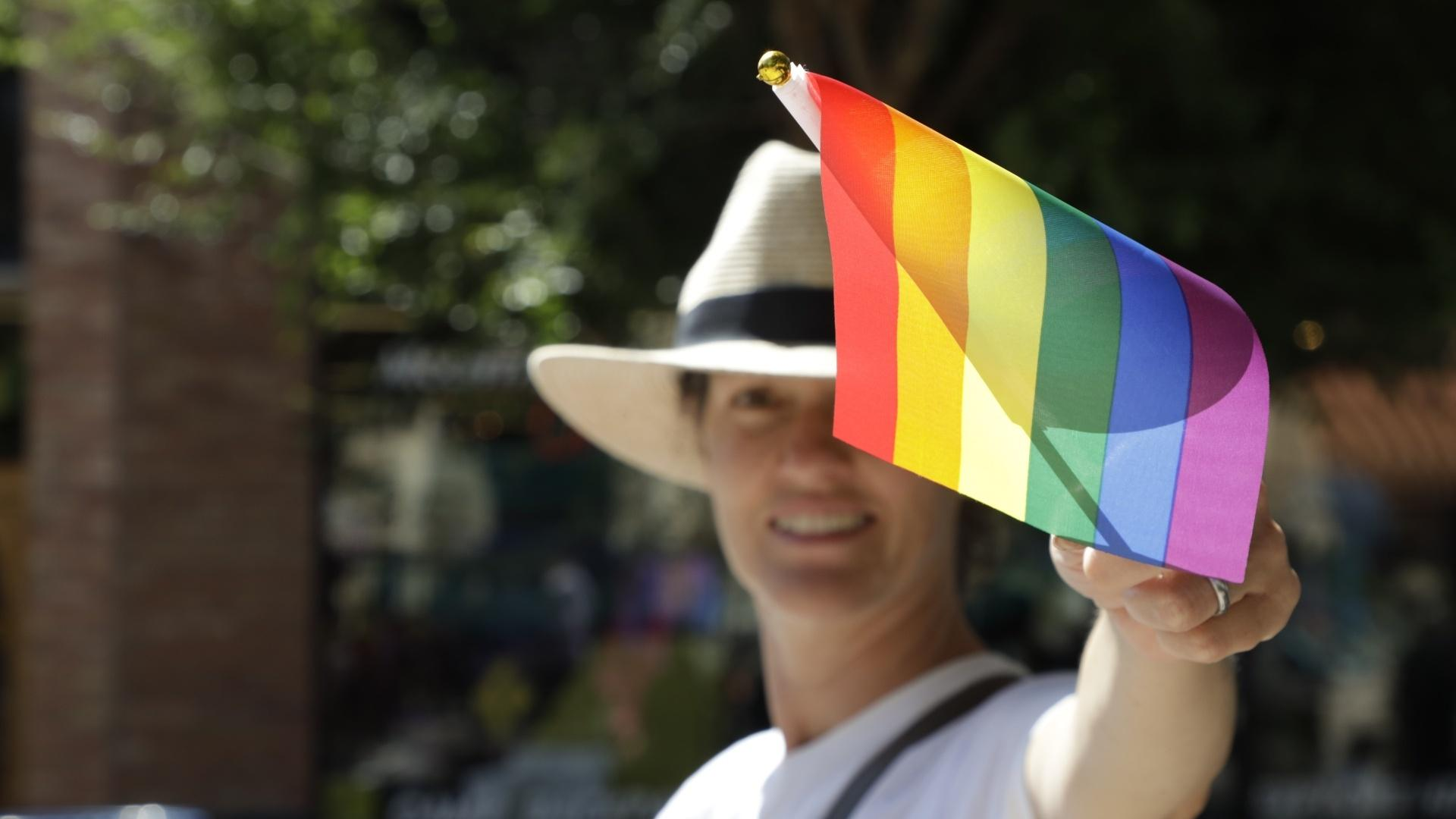 A participant in the Colorado West Pride Fest parade in Grand Junction waves a Pride flag, September 12, 2021.