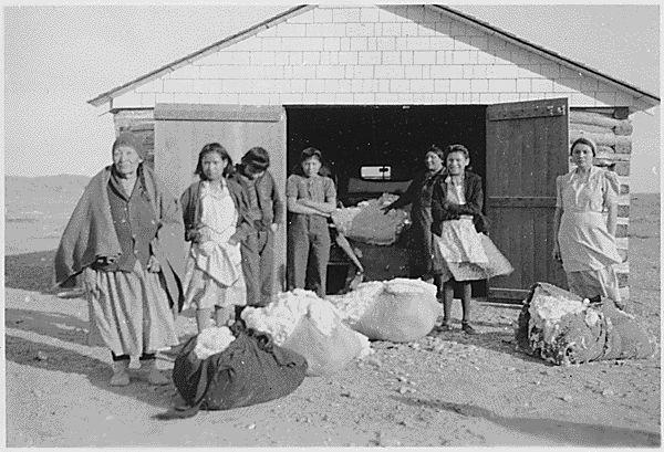 Seven women with bags of wool, 1940