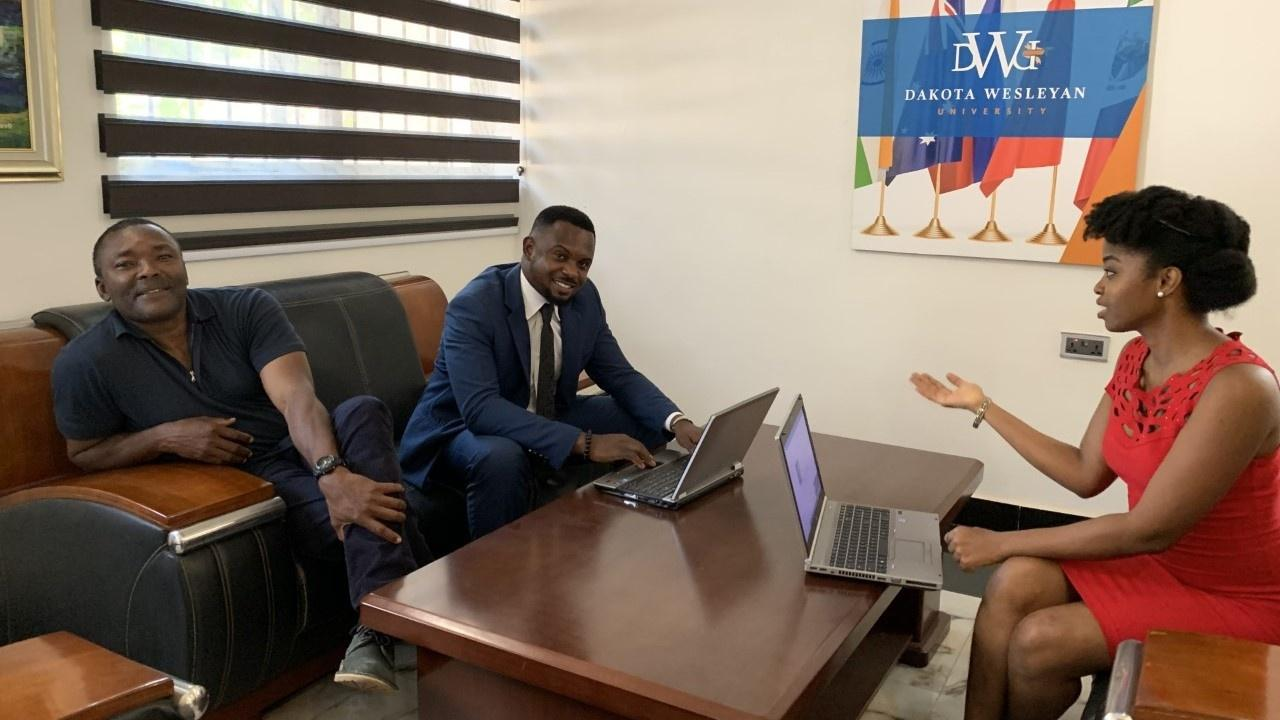 The three staff members of DWU's international recruitment office in Nigeria gather around an office table.