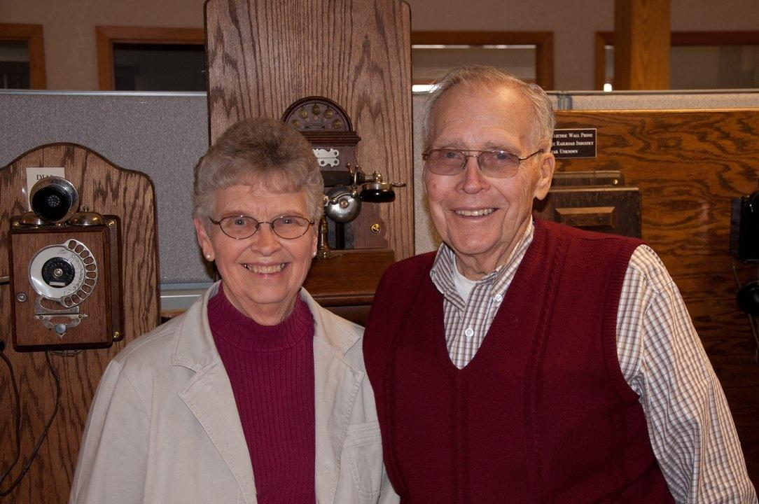 Peg and Frank Gebhardt with their phone collection at the Alamon offices in Kalispell