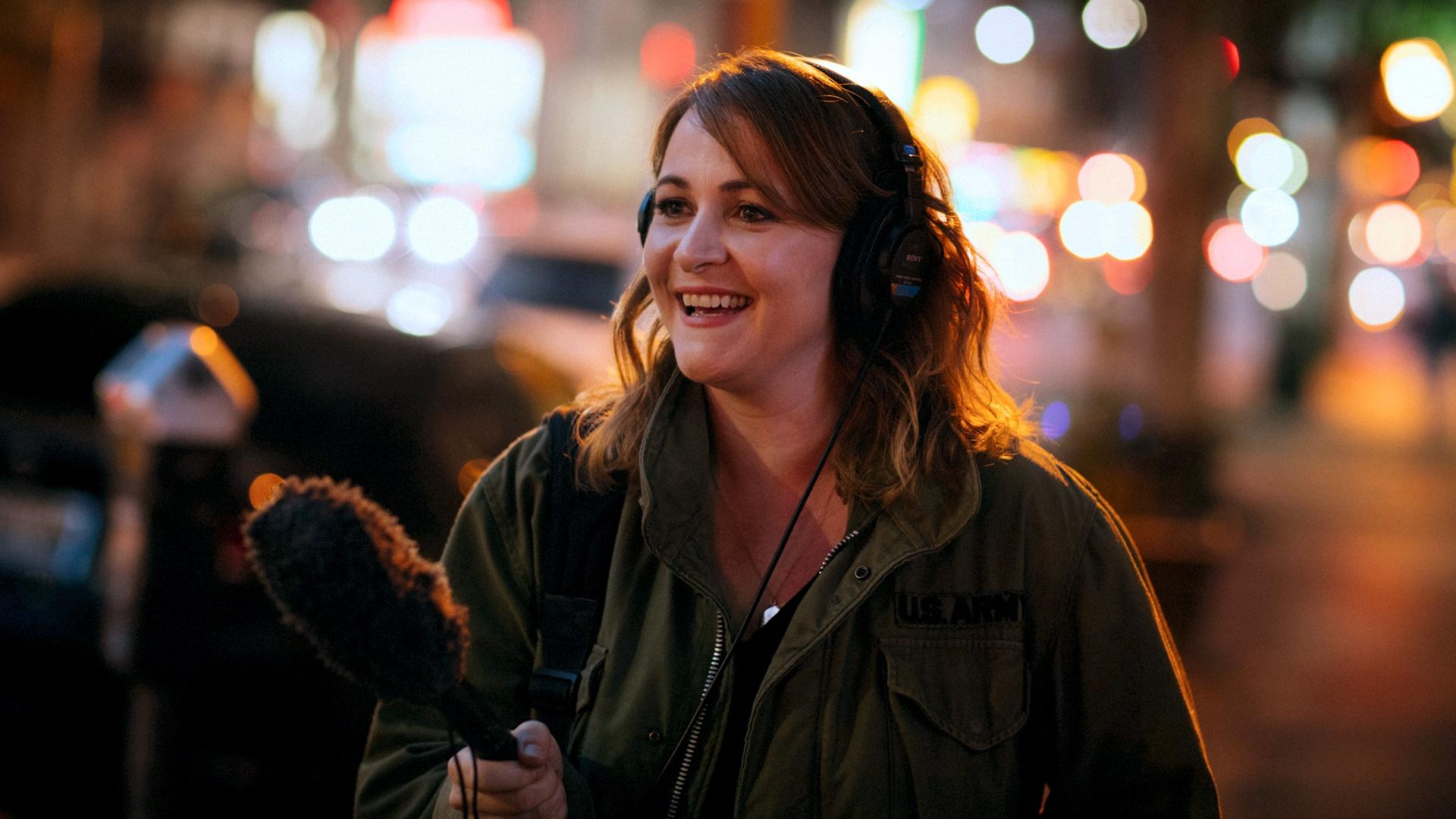 Kelly McEvers smiles. She is wearing headphones and holds a microphone.