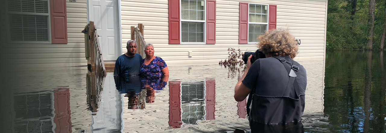 Gideon Mendel photographs a husband and wife. All three are waist-deep in water, and stand in front of a flooded house, after Hurricane Florence hit the Carolinas