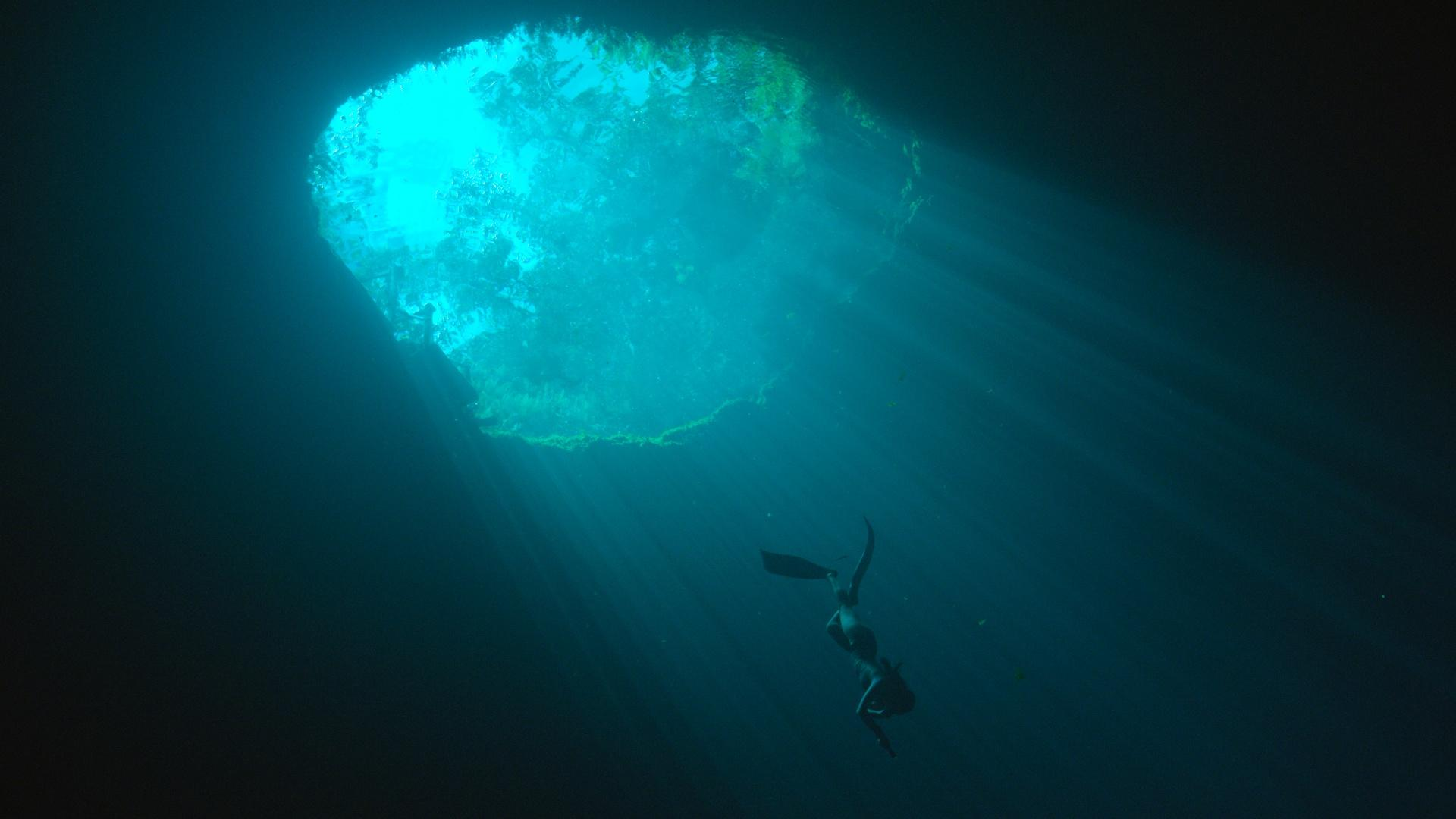 Camilla Jaber dives in a cenote, in the Yucatan, Mexico. A cenote, a small opening of underground water in the jungle can supply whole cities with water.