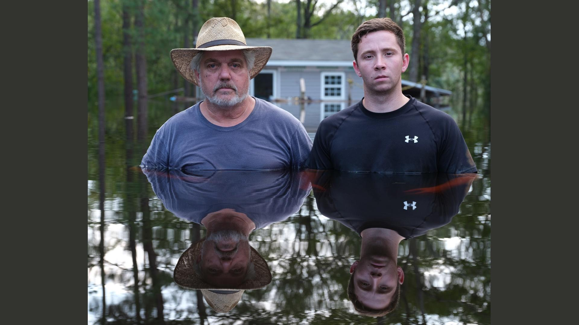 One of Gideon Mendel's photographs from his Drowning World series.  Two men, father and son, stand chest deep in water, after Hurricane Florence hit the Carolinas