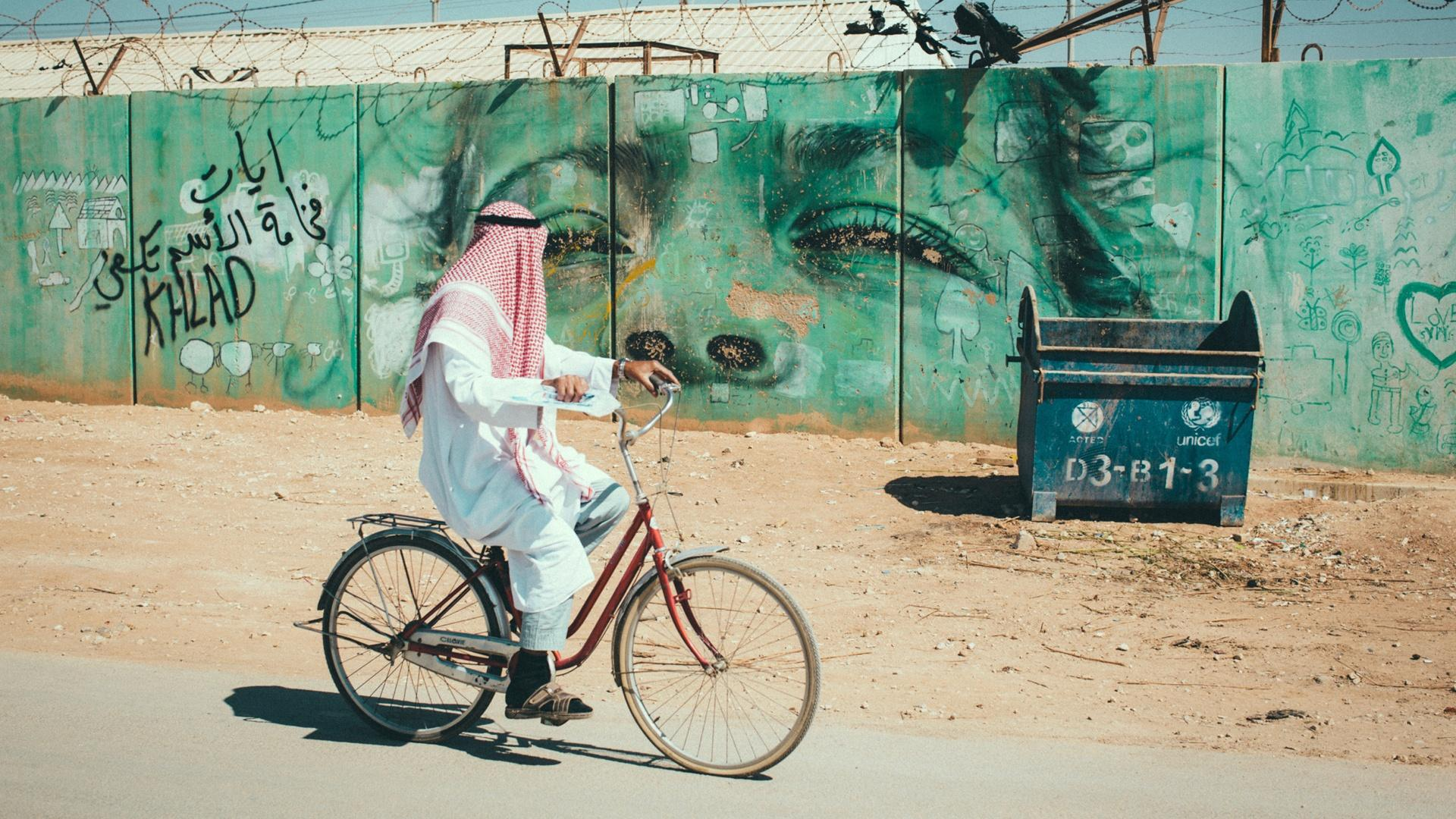 A cyclist, passes graffiti in Gaza, Palestinian Territory. In Gaza, the aquifer is overdrawn and water has been scarce for decades.