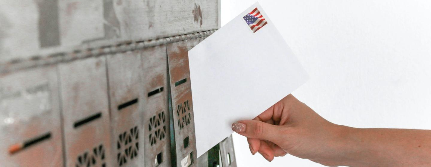 Person places an envelope in a mail box