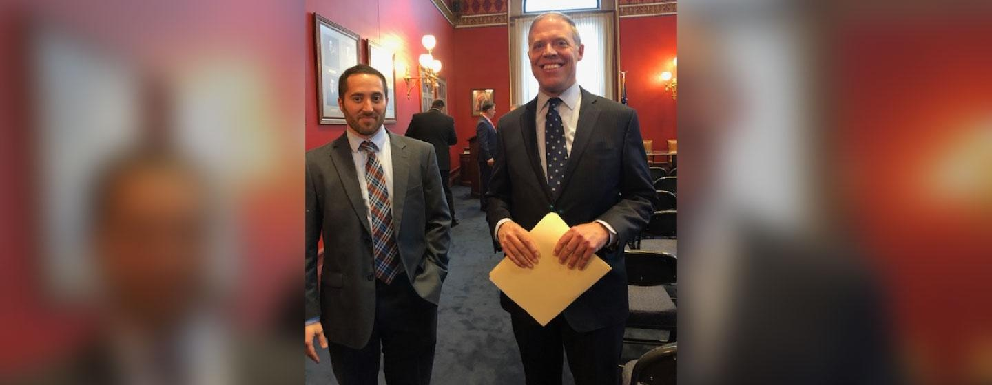 New Assembly Republican leader Will Barclay (Right) standing in a suit and tie while holding a manila folder.