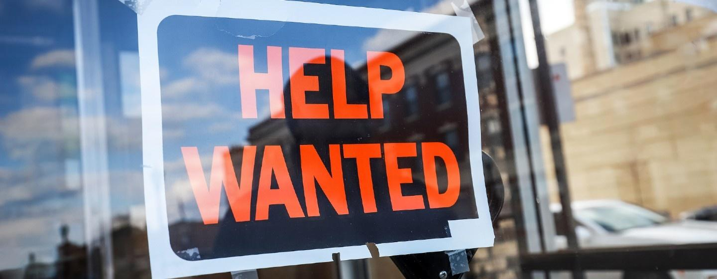 Help Wanted sign taped to a window