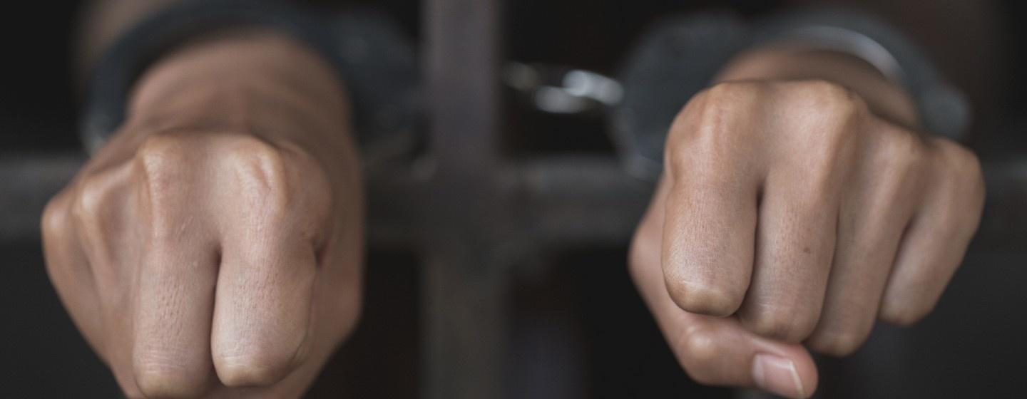Fists with handcuffs through prison bars