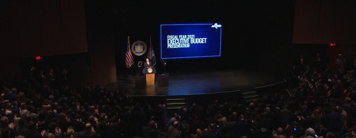 The photo shows the audience seated, facing Governor Andrew Cuomo as he gives the Fiscal Year 2021 Budget Address at the Hart theater.