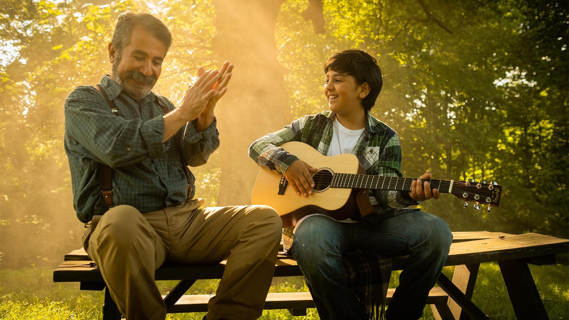 Grandfather teaches guitar to grandson