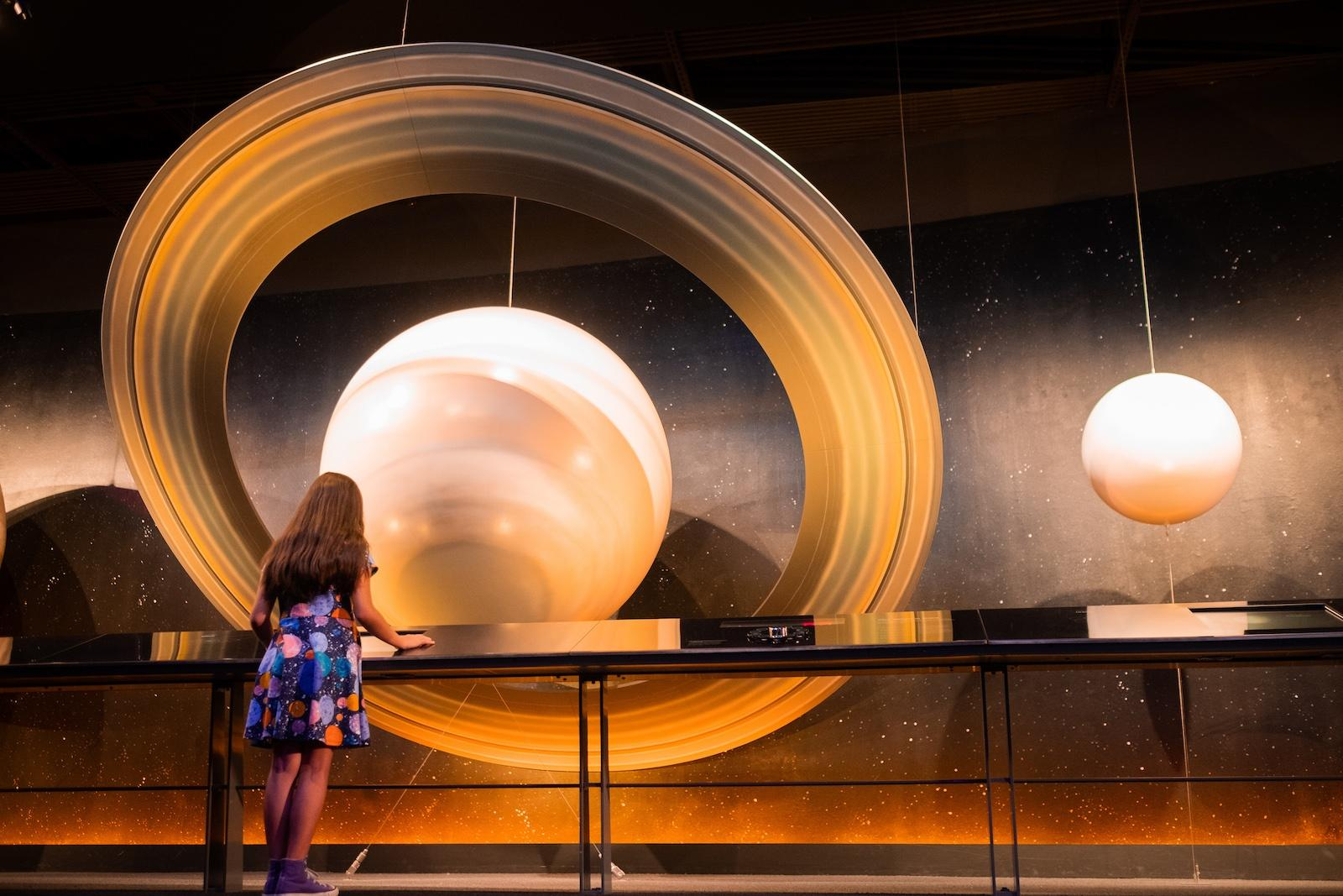 Child stands before large planet display in museum
