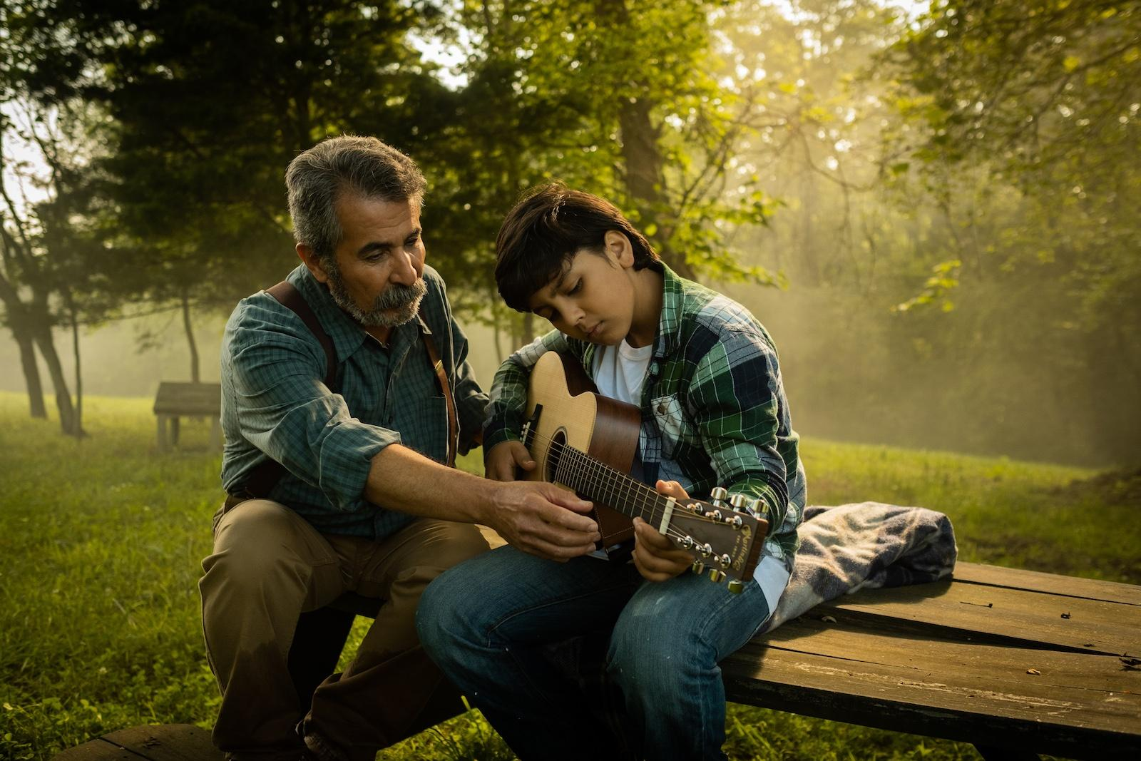 Man instructs child on how to play guitar