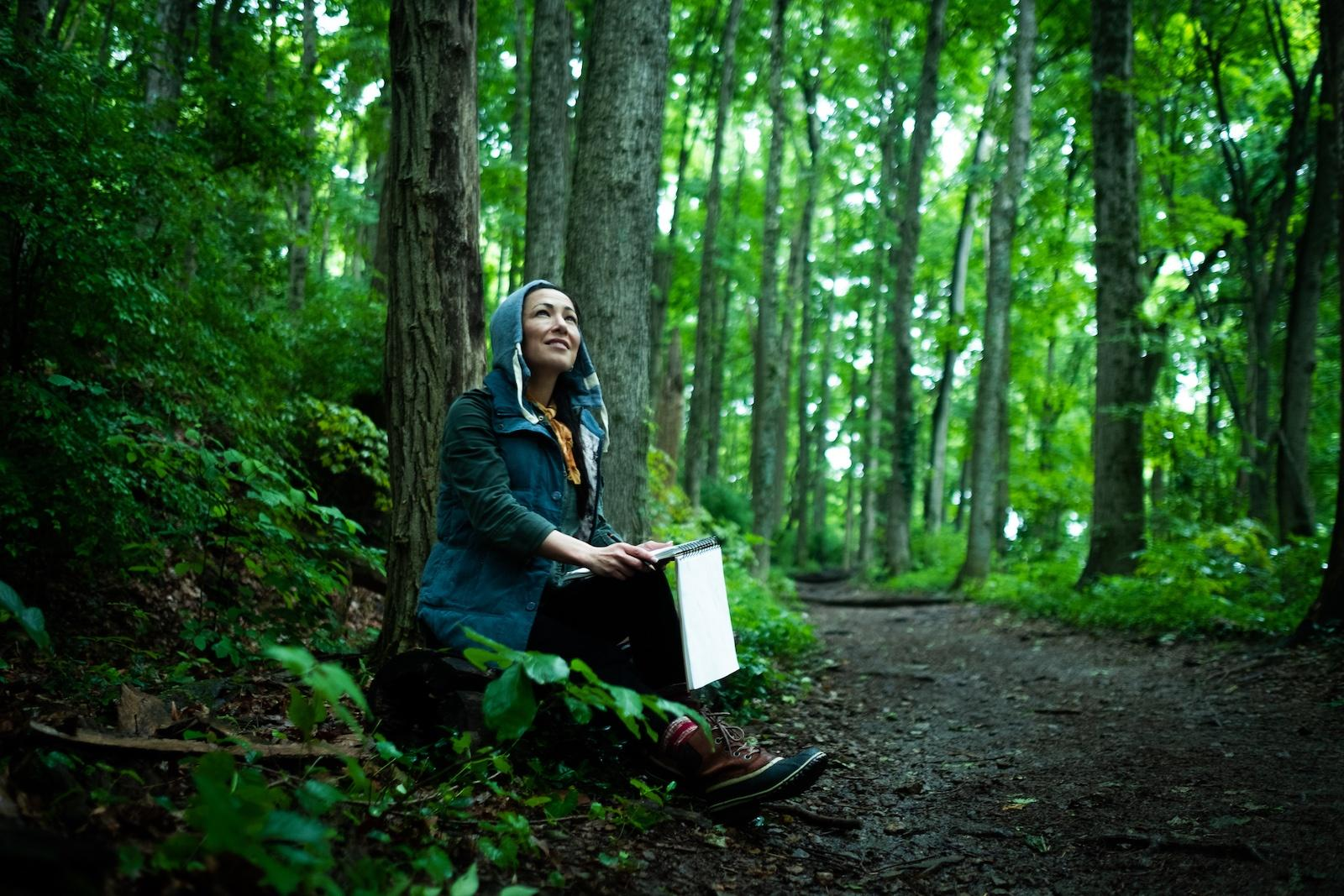 Woman sketches in her journal in the woods